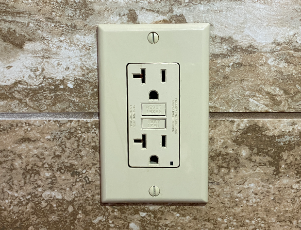 A GFCI outlet and cover mounted on a stone wall