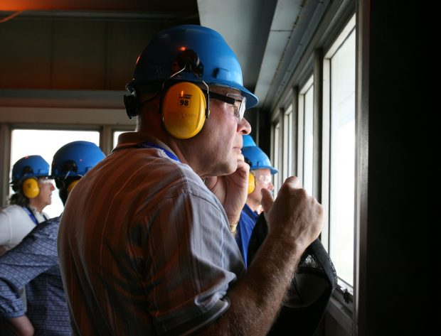 A tour participant listens to the guide at Antelope Valley Station via headphones as he looks out the window for a panoramic view of the coal fired generation station.