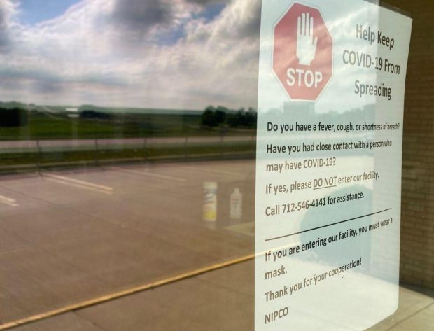 Photo close-up of the warning sign posted on NIPCO's front door about safety protocols before entering the building.