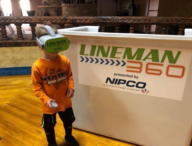 A young boy experiences Lineman 360 by wearing virtual reality goggles