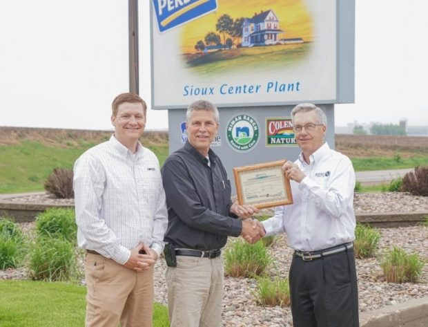 Representatives from NIPCO, Perdue Premium Meats, and North West REC pose in front of the Perdue Premium Meats Company sign, holding the framed renewable energy credt certificate