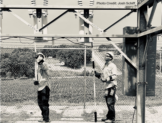 Photo of two NIPCO line workers perform their duties side-by-side