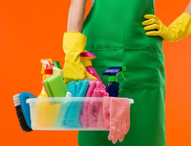 woman with cleaning supplies and rubber gloves