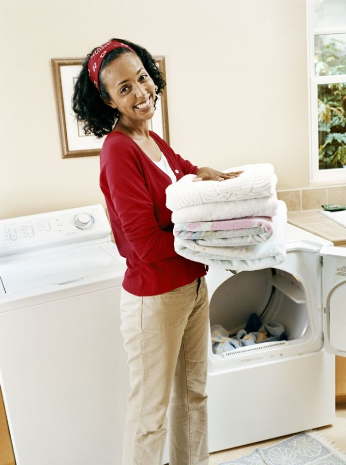 woman folding clothes from a dryer