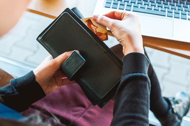 pulling a credit card from a wallet in front of a computer