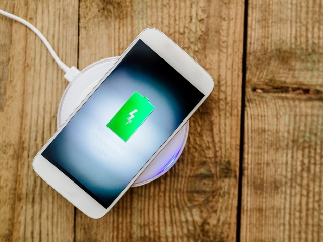 Photo image of a cell phone sitting on a charger.