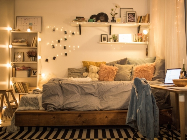 Photo image of an empty bedroom with lights left on.