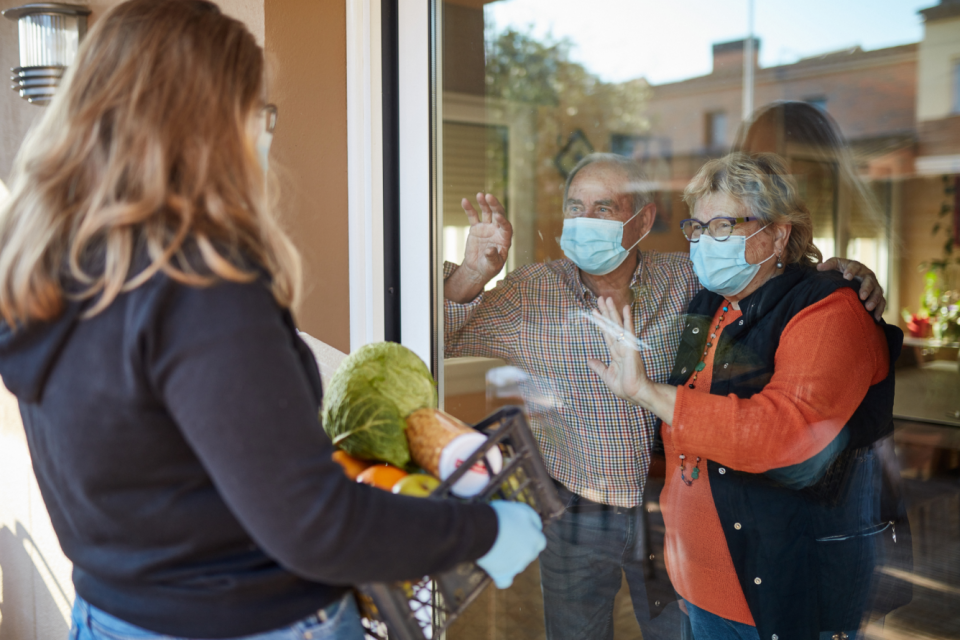 Woman delivering groceries to homebound people with masks on