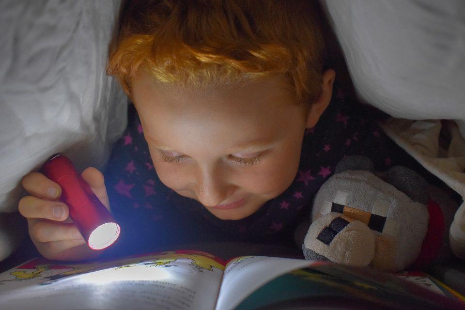child reading by flashlight under a blanket