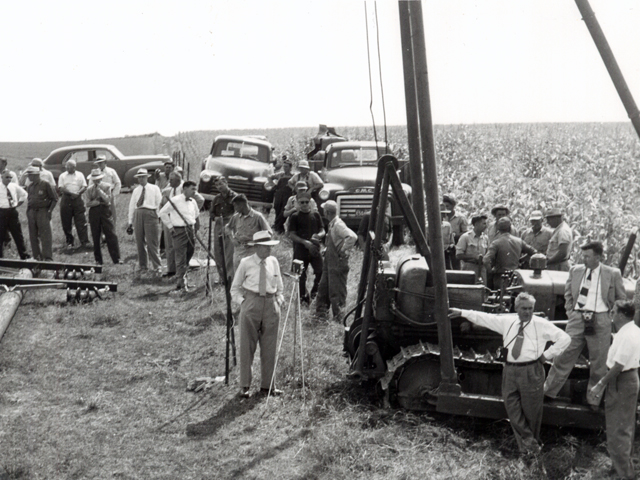 Image is a photo taken of the first pole setting with NIPCO representatives and onlookers.