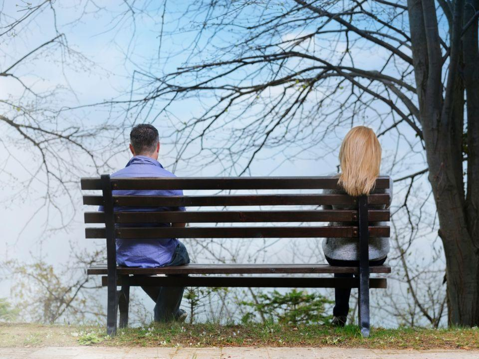 Photo of two people sitting on opposite ends of a park bench.