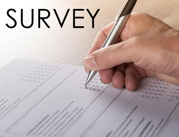 Close-up photo of a hand, holding a pen taking a survey