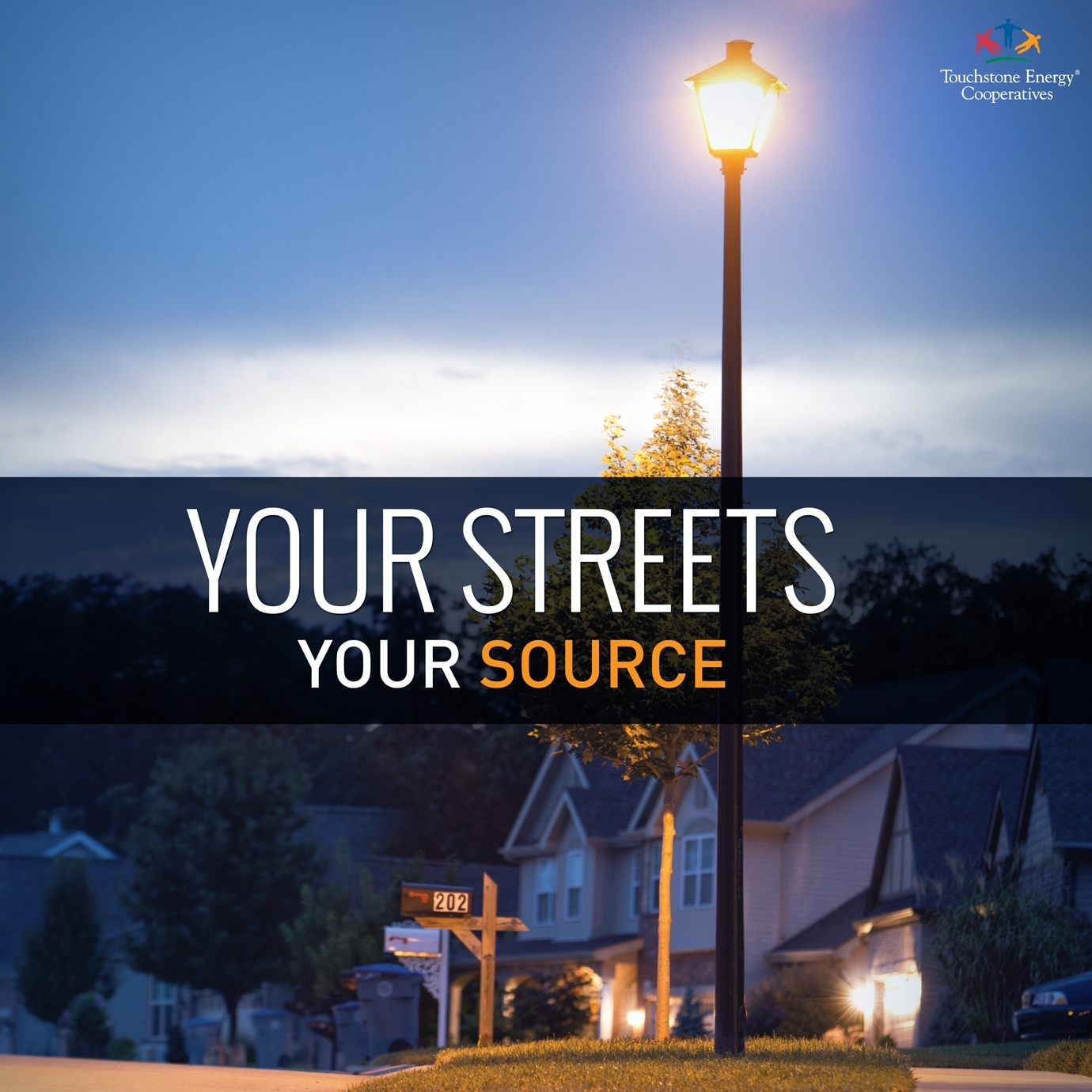 Image features a residential street-scape at dusk with the street lights turned on.
