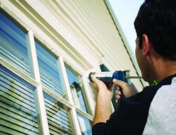 male homeowner caulking a window