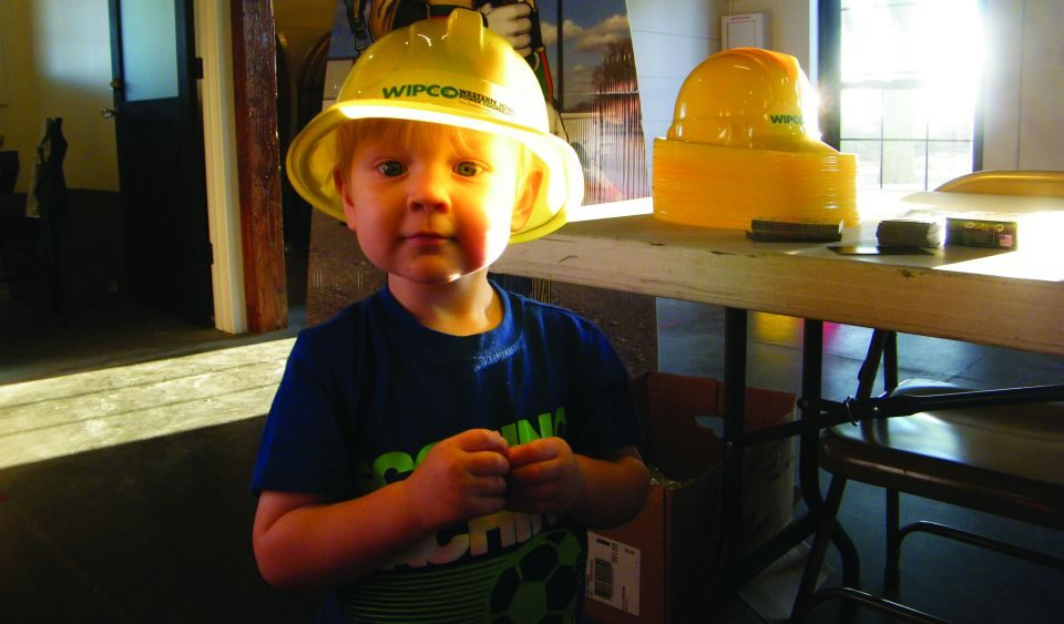 A young child wearing a plastic hard hat.