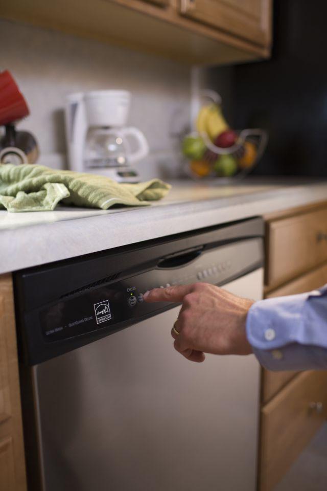 Turning on the dishwasher.