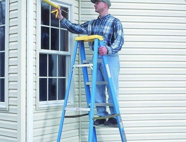 man on ladder caulking