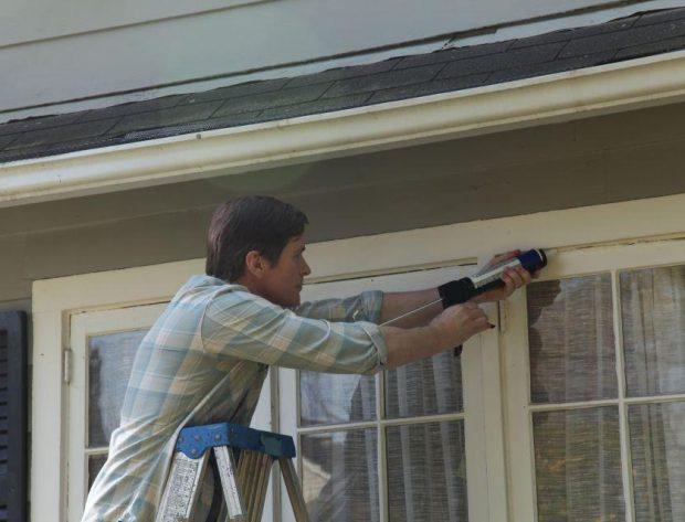 Man on ladder caulking around a window