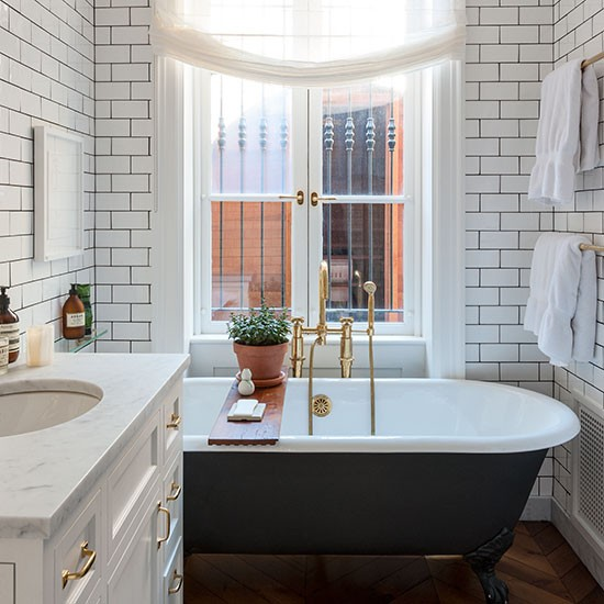 White tiled bathroom with black claw foot tub via house to home