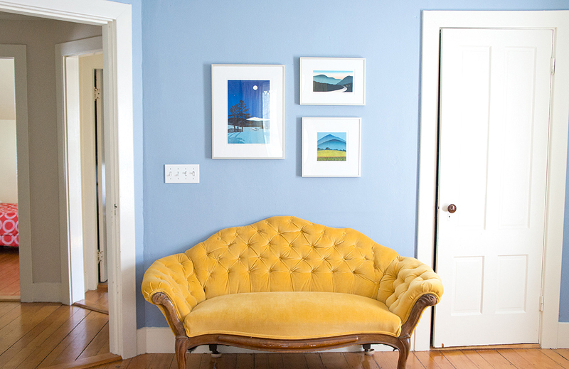 personality infused master bedroom with little yellow couch