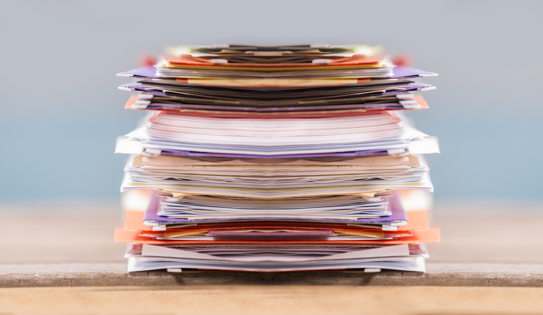 Large stack of multi-colored files and paperwork on an office desk. Blue window background. Business themes. No people.
