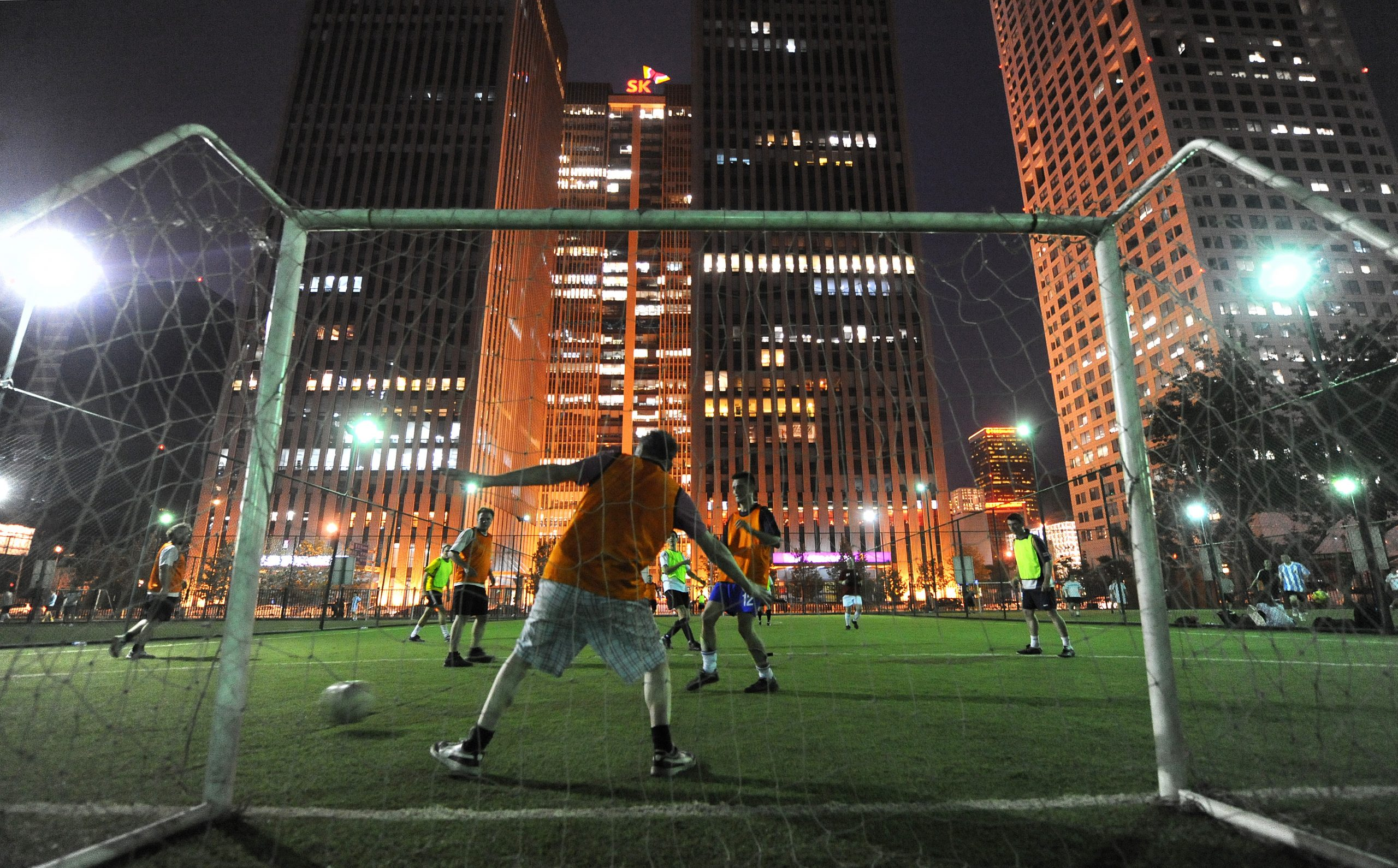 A five-a-side pickup game takes place under floodlights on an artifical grass pitch beneath office towers in Beijing on June 9, 2010. World Cup fever is sweeping across Asia as hundreds of millions of fans in the football-mad region count down to the June 11 start of an event that's a surefire winner for pubs, clubs and bookmakers. AFP PHOTO/Frederic J. BROWN (Photo credit should read FREDERIC J. BROWN/AFP/Getty Images)
