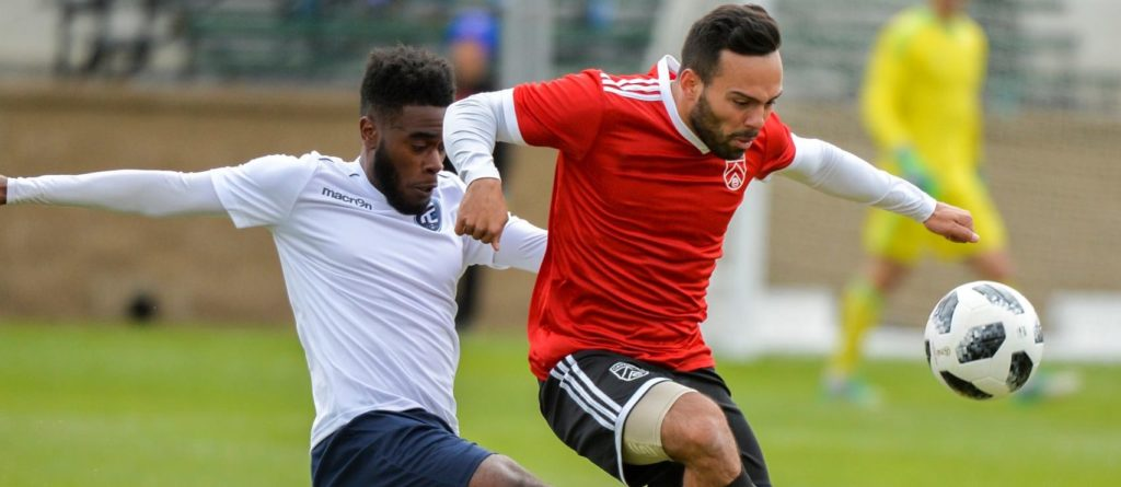 FC Edmonton's Allan Zebie and Cavalry's Sergio Camargo battle for the ball in a 2018 'Al Classico' friendly.