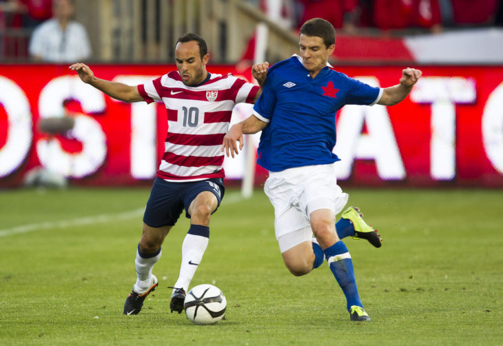 Canada's Will Johnson (R) battles for the ball with former U.S. star Landon Donovan. (Canada Soccer)