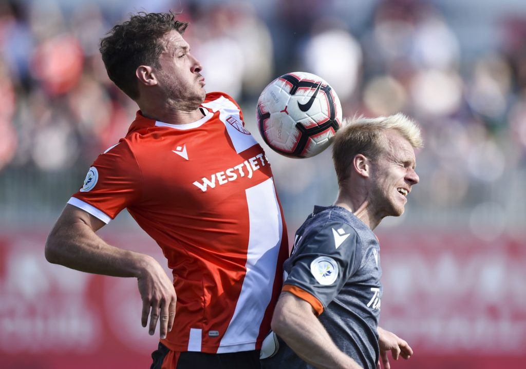 Mason Trafford of Cavalry FC goes up for the ball with Kyle Bekker of Forge FC. (Photo: Mike Sturk/CPL).