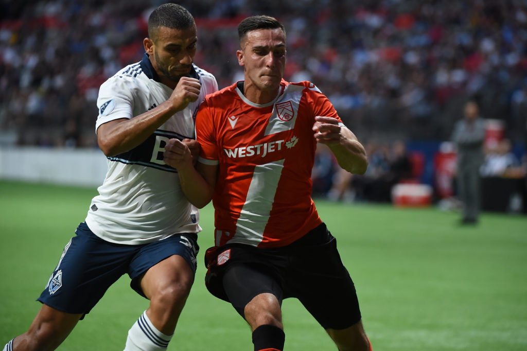 Jul 24, 2019; Vancouver, British Columbia, Canada; Vancouver Whitecaps defender Ali Adnan (53) challenges Cavalry FC defender Dominick Zator (4) during the first half at BC Place Stadium. Mandatory Credit: Anne-Marie Sorvin-USA TODAY Sports
