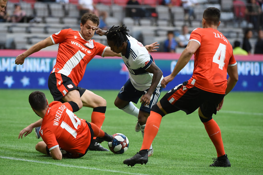 Jul 24, 2019; Vancouver, British Columbia, Canada; Vancouver Whitecaps midfielder Yordy Reyna (29) battles for the ball against Cavalry FC defender Jonathan Wheeldon (14) and defender Dominick Zator (4) during the first half at BC Place Stadium. Mandatory Credit: Anne-Marie Sorvin-USA TODAY Sports
