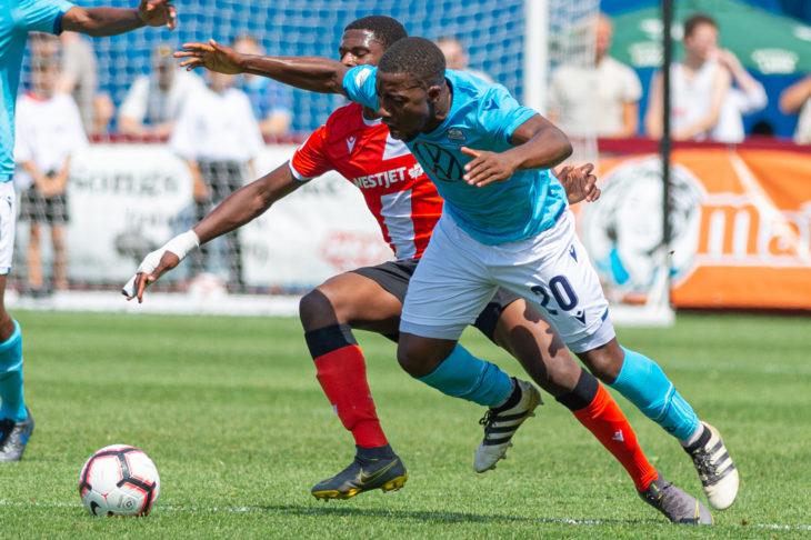 HFX Wanderers FC midfielder Ndzemdzela Langwa gets tangled up with a Cavalry FC's Elijah Adekugbe. (Trevor MacMillan/CPL).