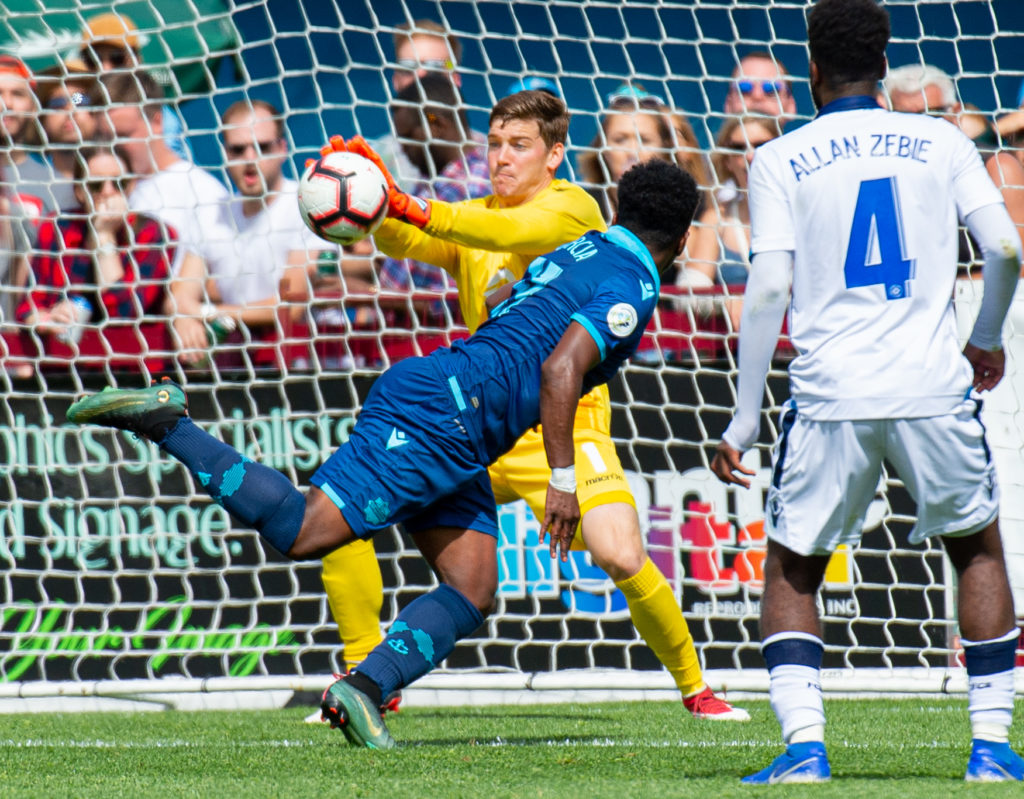 FC Edmonton goalkeeper Connor James makes the save on HFX Wanderers FC attacker Akeem Garcia. (Trevor MacMillan/CPL).