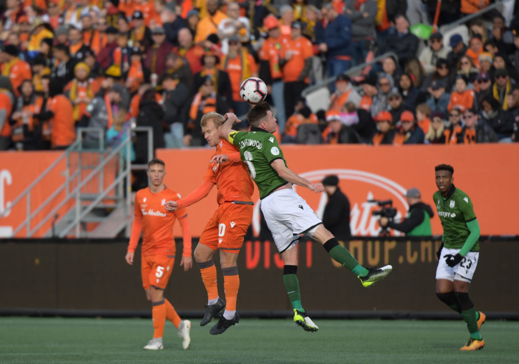 Forge FC midfielder Kyle Bekker and Cavalry FC midfielder Nik Ledgerwood battle for the ball in the first half of a Canadian Premier League Finals at Tim Hortons Field. Mandatory Credit: Dan Hamilton-USA TODAY Sports for CPL