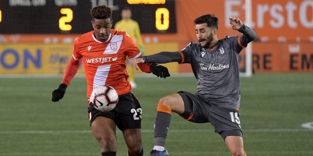 Oct 16, 2019; Hamilton, Ontario, CAN; Cavalry FC forward Dominique Malonga (23) tries to get past Forge FC midfielder Tristan Borges (19) in the second half of a Canadian Premier League soccer match at Tim Hortons Field. Mandatory Credit: Dan Hamilton-USA TODAY Sports for CPL