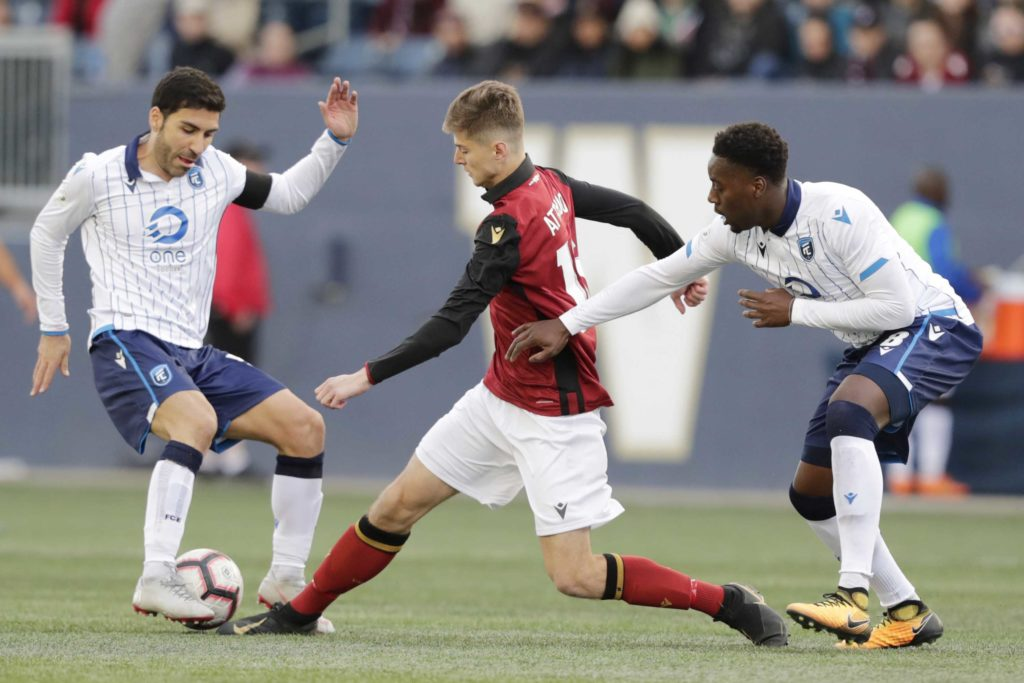 May 4, 2019; Winnipeg, Manitoba, CAN; Valour FC attacker Tyler Attardo (16) splits between FC Edmonton defender Ramón Soria (5) and FC Edmonton defender Mélé Temguia (8) in the second half during a Canadian Premier League soccer match at Investors Group Field. Mandatory Credit: James Carey Lauder-USA TODAY Sports for CPL