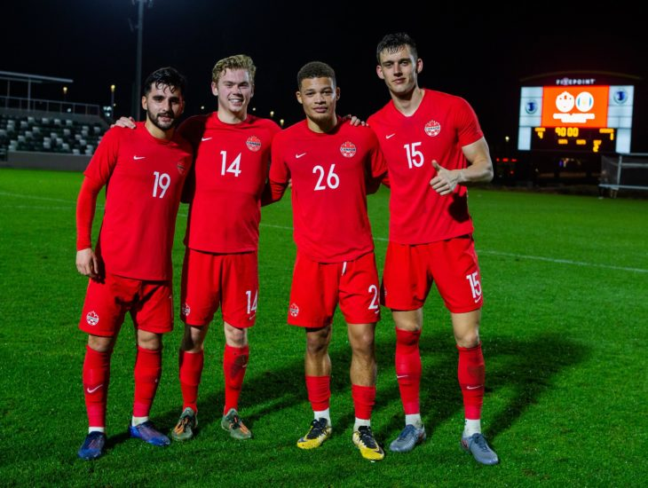 Tristan Borges, Jacob Shaffelburg, Zorhan Bassong and Amer Didic pose after Friday's win over Barbados. (Canada Soccer photo)