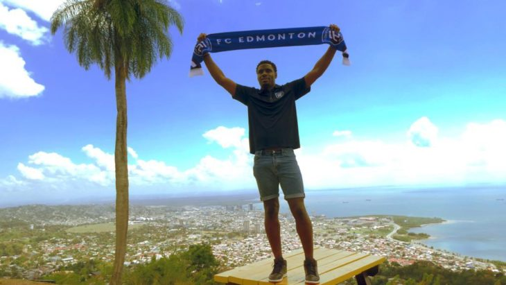 Kareem Moses proudly holds up an FC Edmonton scarf