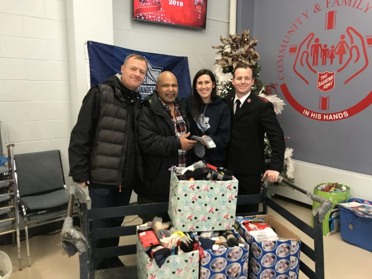 Calvin Gill in between Gareth Hampshire (left) and Danae Iatrou (right) with Capt. Jamie Locke from the Salvation Army.