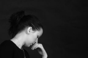 A girl in deep thought signifying suicide consideration