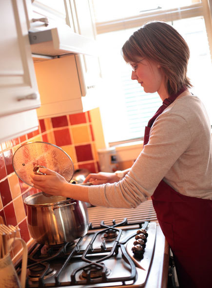 woman cooking at stove with backsplash