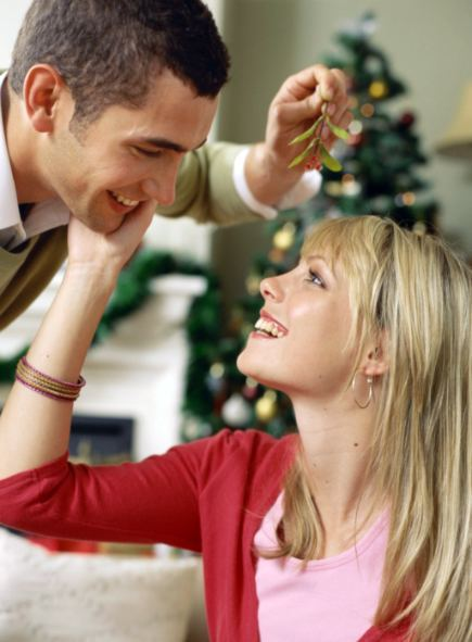 couple kissing under mistletoe decoration