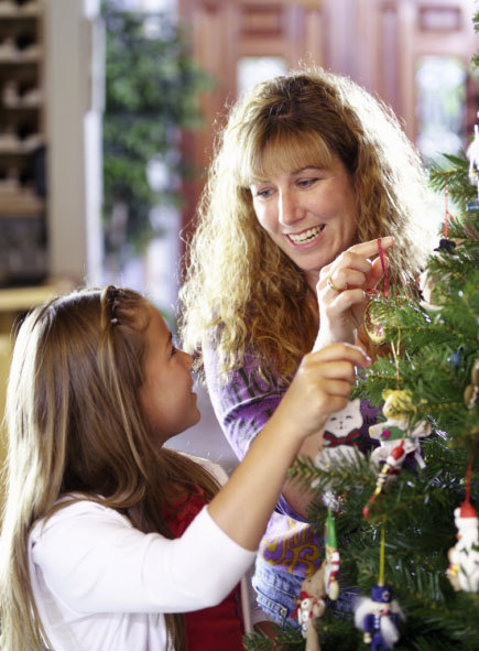 mother daughter hanging Christmas ornaments