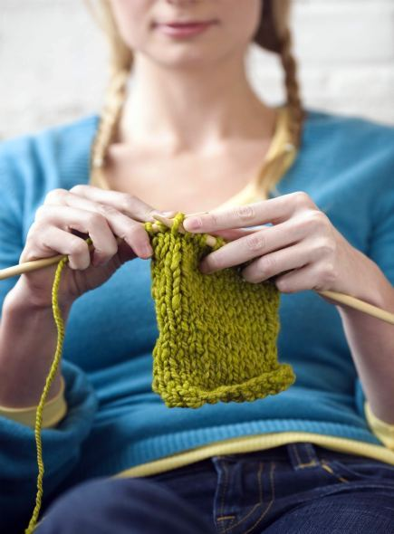 woman holding knitting needles