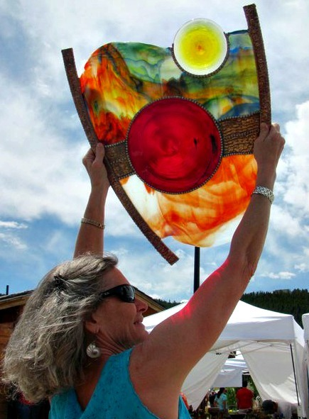 Claudia Ariss displaying her prize-winning stained glass piece at the High Peaks Art Festival