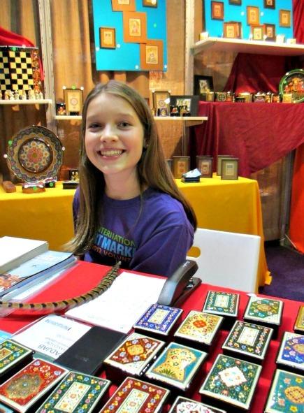 Sante Fe International Folk Art Market girl displaying some wares