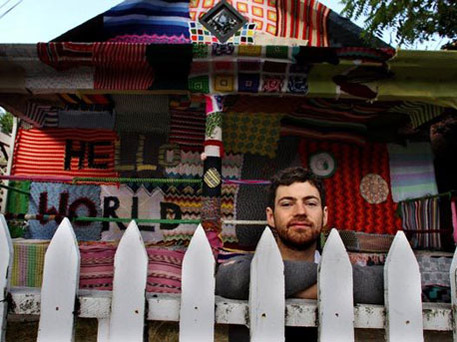Artist Luke Haynes in front of a quilted house