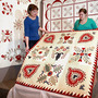 women hold up quilt