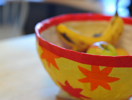 A yellow bowl made of paper mache, with a red rim and an orange sunburst pattern
