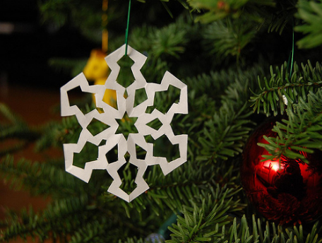Close-up of a paper snowflake hanging from a Christmas tree